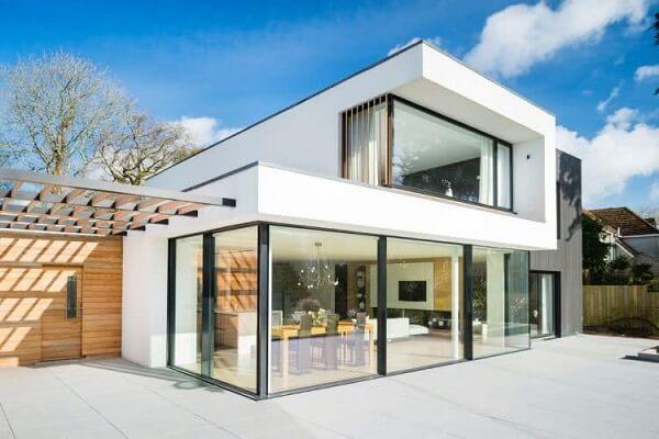 Casa sobrado simples com fachada branca, painéis de vidro e janelas fixadas com estrutura metálica preta