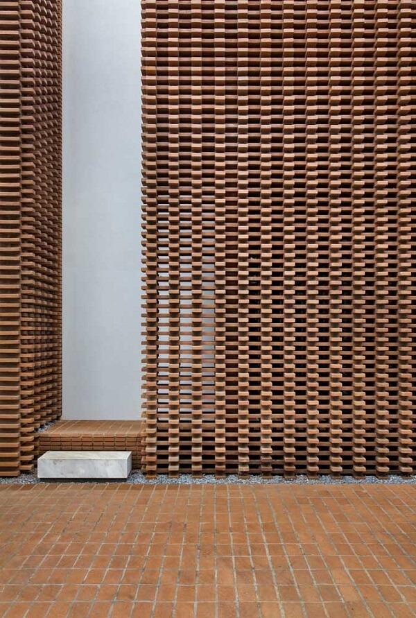 Decoração de muro com peças de madeira criando um visual vazado