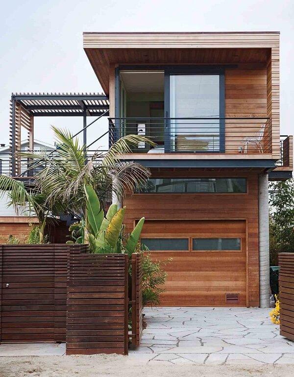 Fachada de casa sobrado com portão de madeira