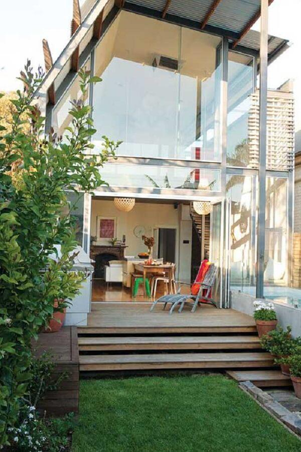 Fundos da casa sobrado pequena toda em vidro favorece a luz natural