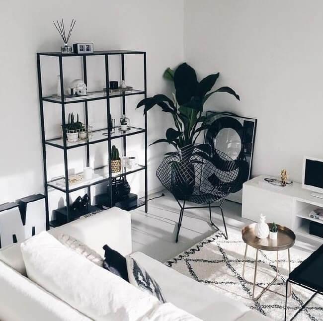 Estantes, vasos, mesas de centro e cadeiras, quando mais escuras, são perfeitas para criar um equilíbrio visual entre preto e branco