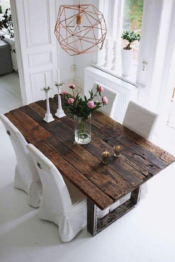 Lustre aramado e cores de madeira escura para mesa se destacam no ambiente