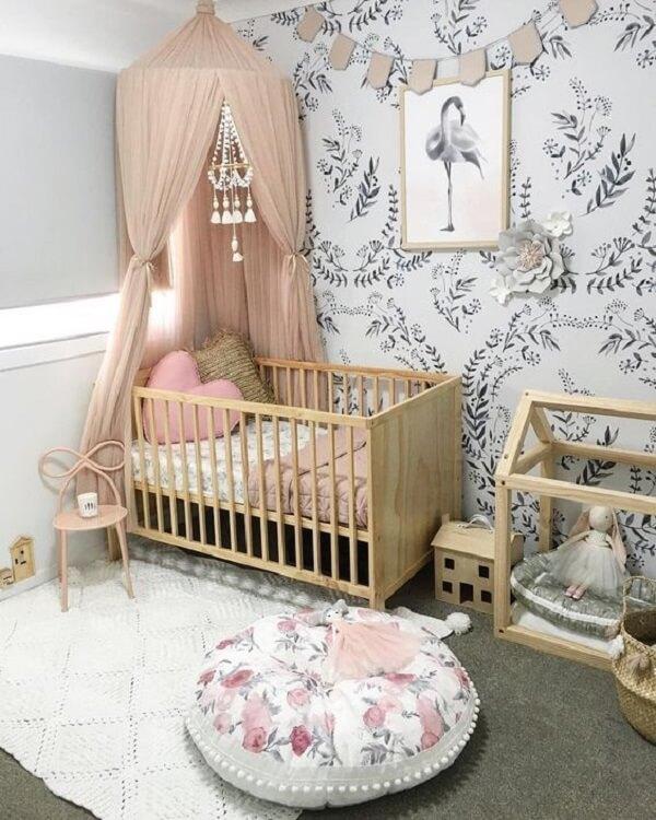 Modelo de berço cor de madeira crua e puff redondo estampado decoram o quarto de bebê