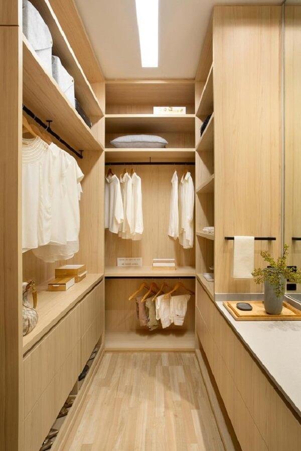 Modelo de guarda-roupa cor madeira com design planejado para closet