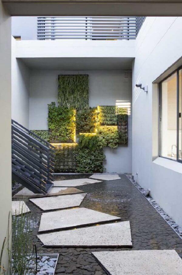 Muro interno decorado com pequenos quadrados e cada um sendo iluminado por uma faixa de LED