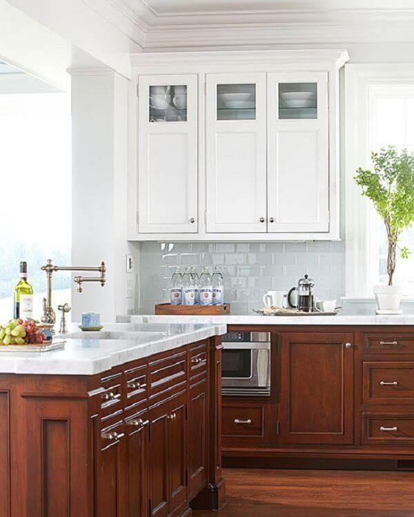 O armário de cozinha cor de madeira escura com tampo de granito branco encantam a decoração