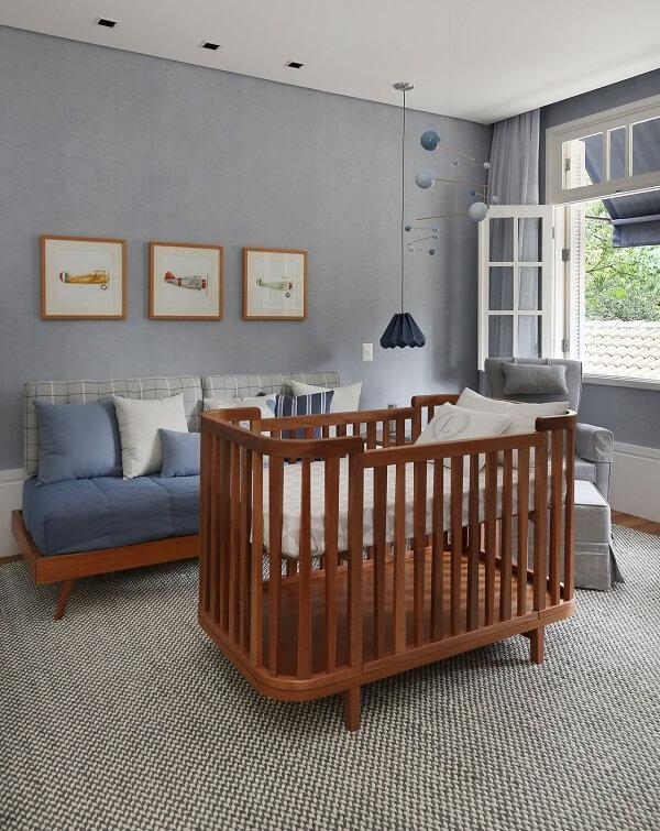 O berço cor de madeira quebra a frieza do tom cinza do quarto de bebê