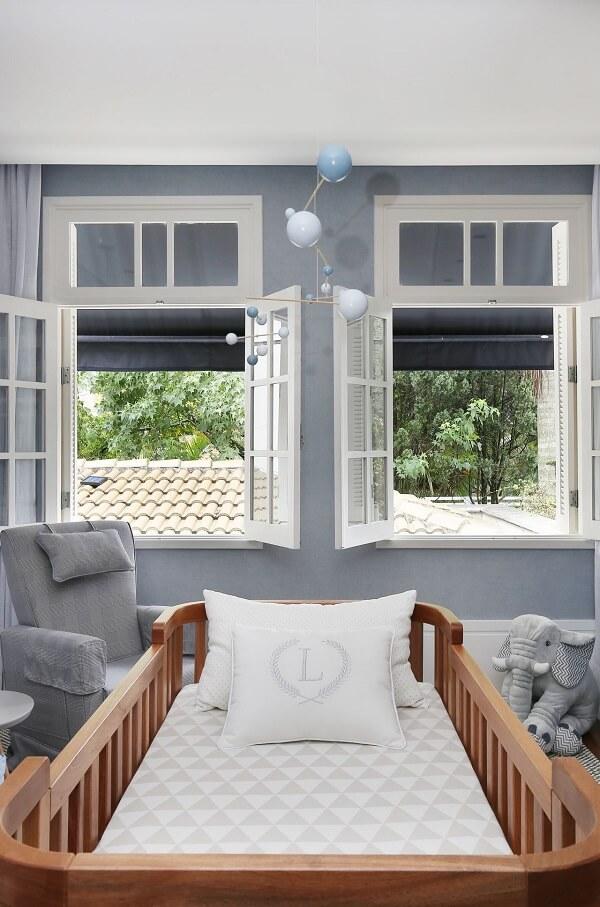 O berço cor de madeira traz aconchego para o quarto do bebê em tom cinza