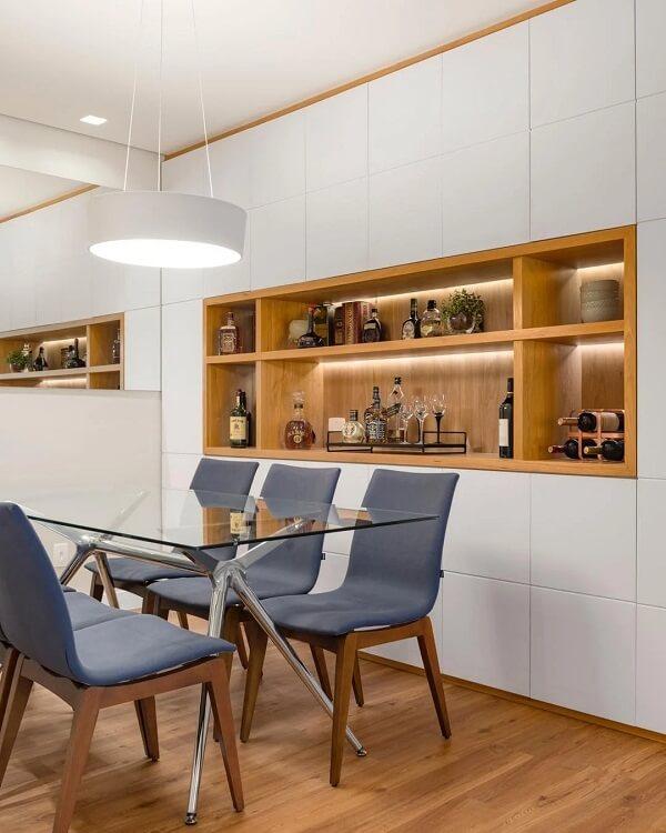 O piso cor de madeira traz um toque rústico para o ambiente da sala de jantar
