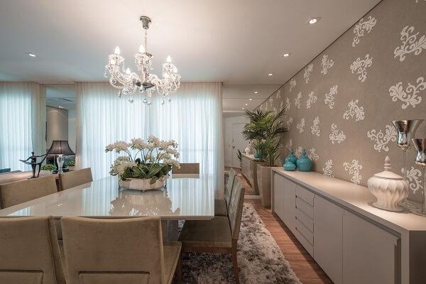 O tapete shaggy marrom delimita todo espaço da mesa de jantar branca