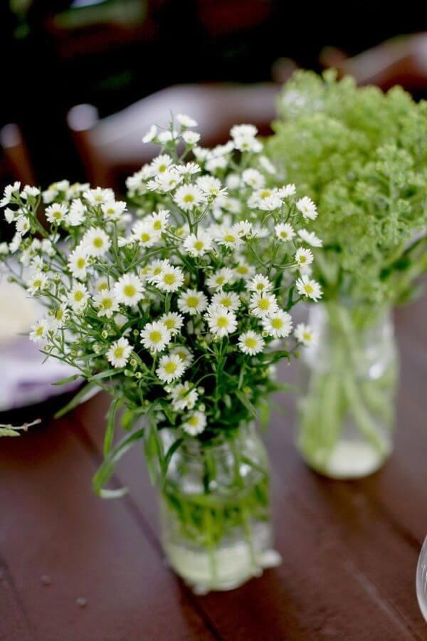 O vaso de vidro com mini margarida decora o centro da mesa