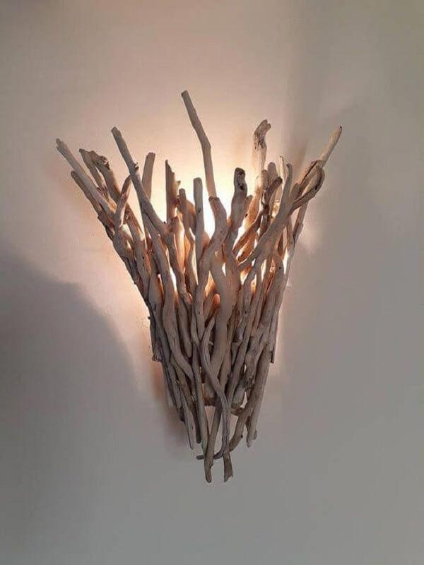 Os gravetos dão vida a uma linda arandela de madeira