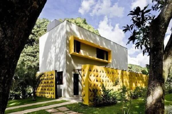 Os muros modernos de cobogó amarelo combinam com os detalhes arquitetônicos