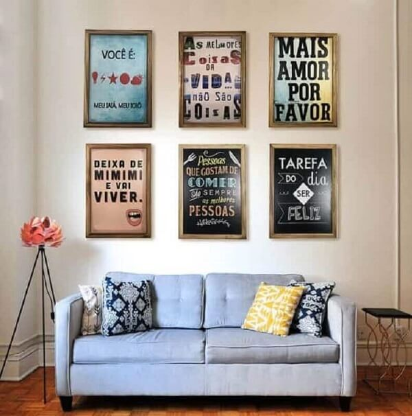 Placas decorativas com frases foram enquadradas e fixada acima do sofá da sala