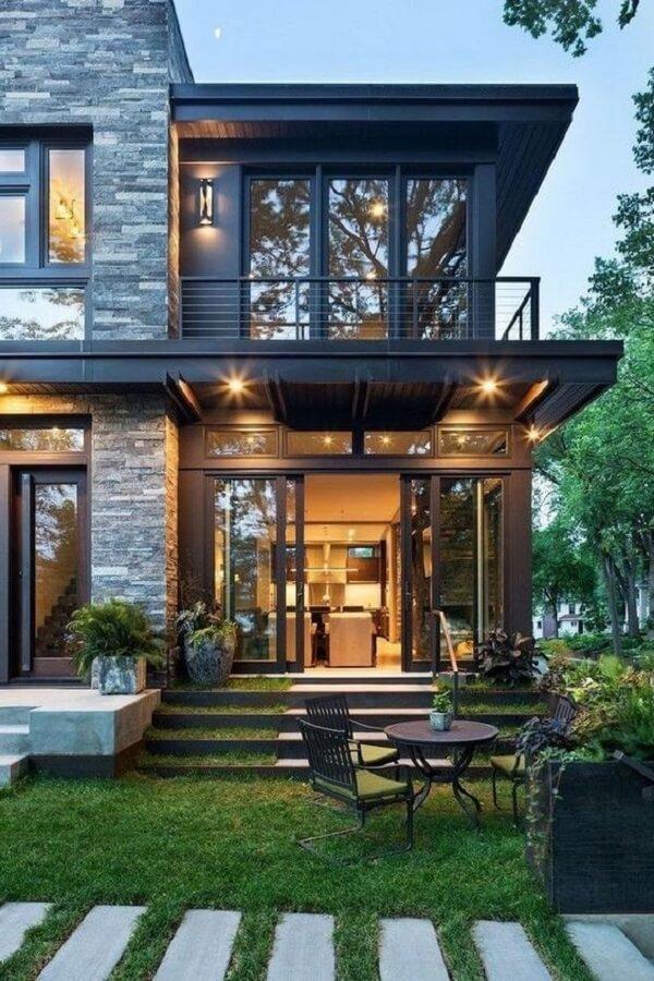 Projeto de casa sobrado com cadeiras estofadas verdes e mesa metálica preta
