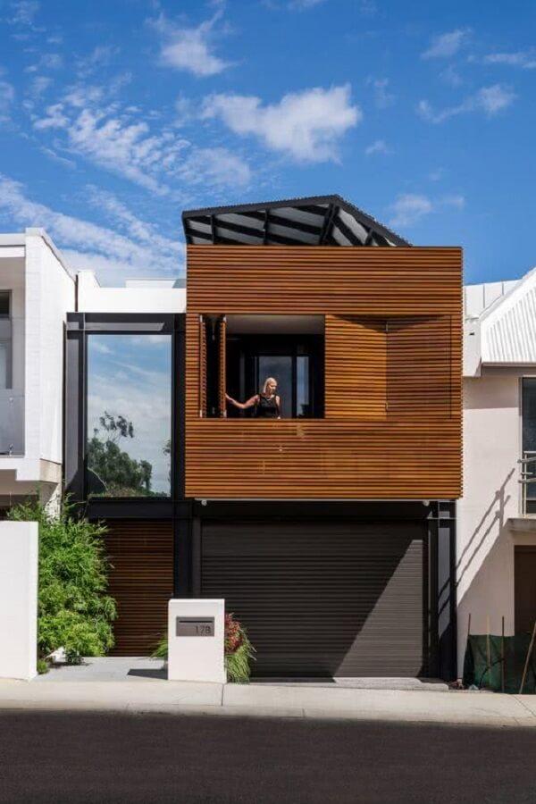 Projeto de casa sobrado com revestimento em ripas de madeira na fachada