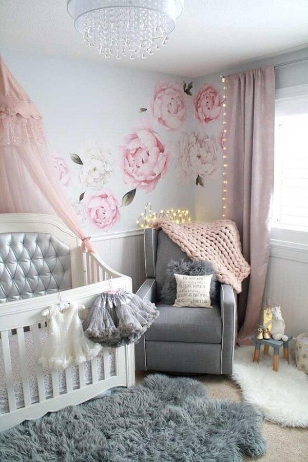 Tons de cinza e rosa se dispersam em vários objetos e móveis do quarto de bebê