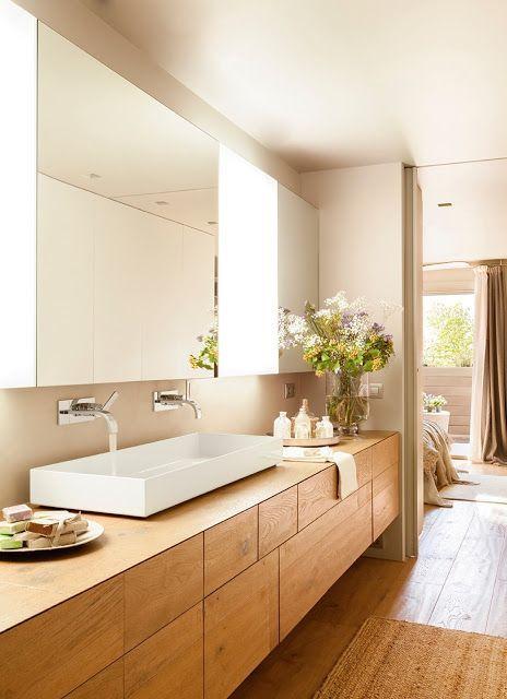 Banheiro grande com móveis de madeira e cuba branca