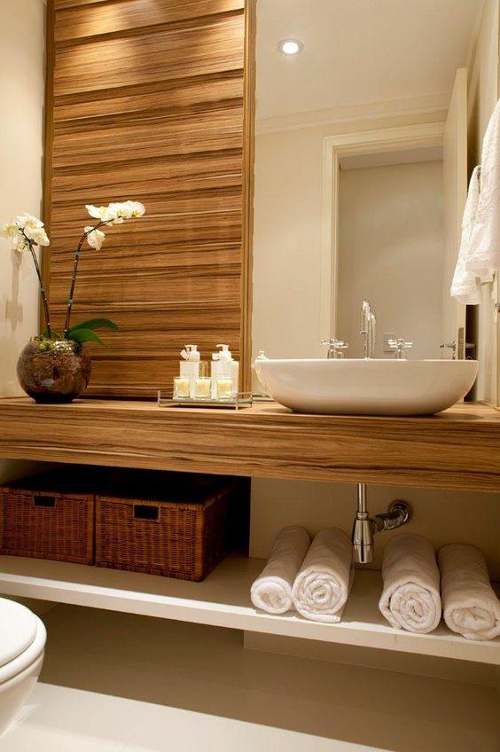 Banheiro amadeirado com bancada da mesma cor que a parede