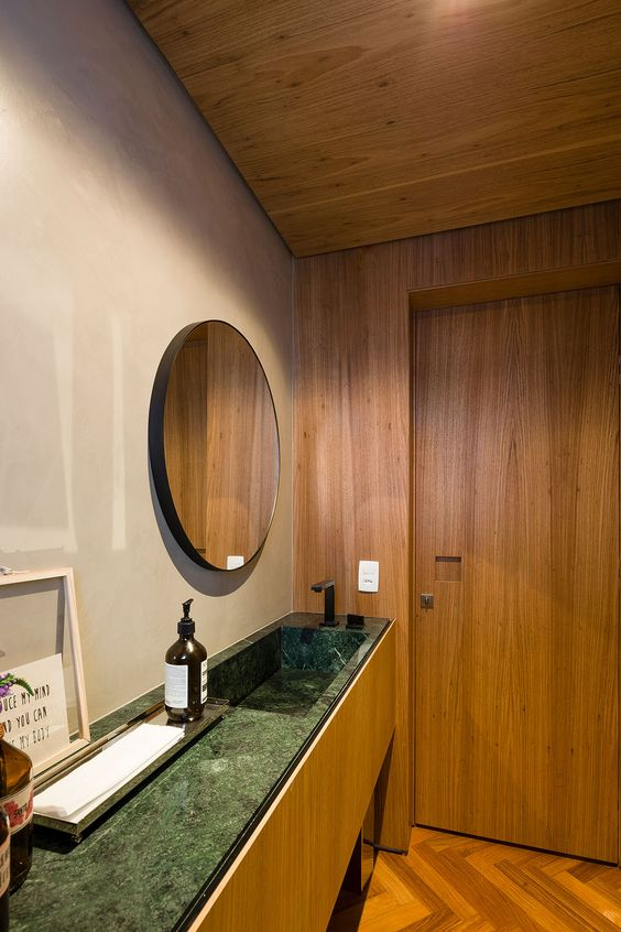 Banheiro amadeirado com espelho redondo