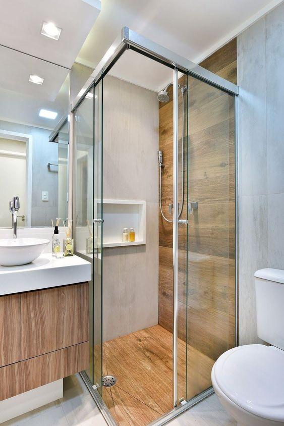 Banheiro amadeirado pequeno e chuveiro cromado