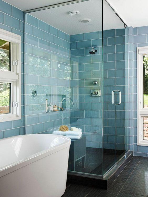 Banheiro com revestimento azul turquesa e banheira branca