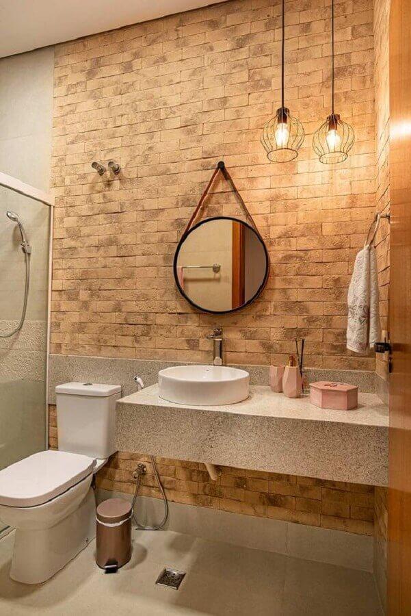 banheiro decorado com parede de tijolo e espelho redondo com moldura e alça Foto Casa de Valentina