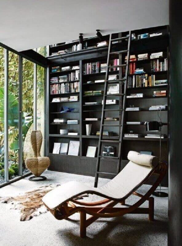 cantinho de leitura decorado com estante preta planejada e poltrona confortável para leitura Foto Next Luxury