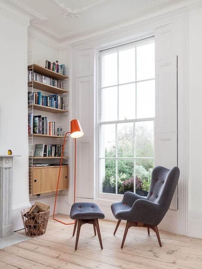 cantinho de leitura simples decorado com luminária laranja e poltrona com puff para leitura cinza Foto Archilovers