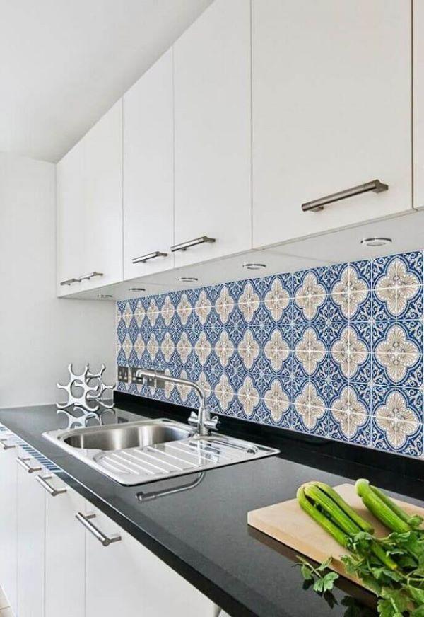 Cozinha decorada com armário brancos e azulejo azul