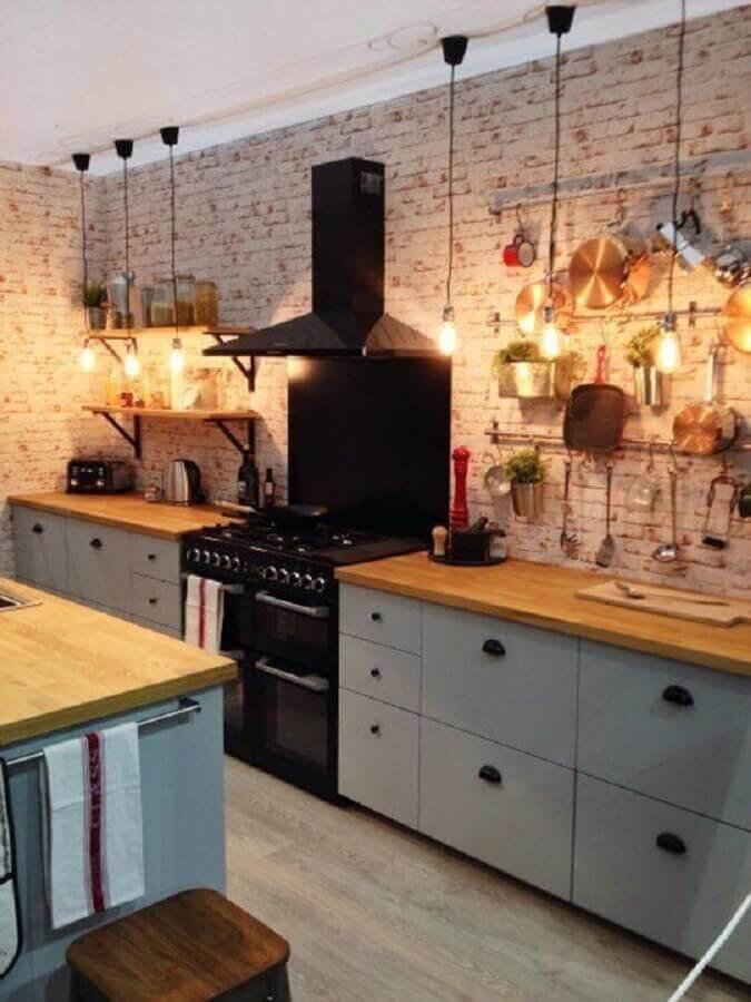 cozinha planejada estilo industrial decorada com bancada de madeira e parede de tijolinho Foto Apartment Therapy