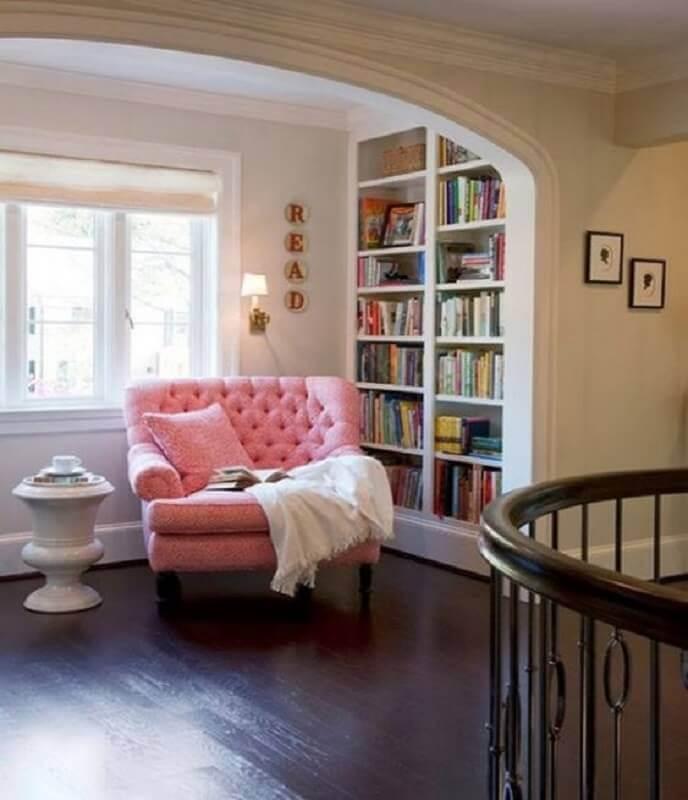 decoração clássica com estante de livros planejada e poltrona confortável para leitura cor de rosa Foto Pinterest
