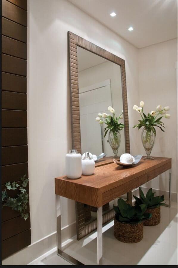 decoração de hall de entranda com espelho grande com moldura e aparador de madeira  Foto Duca Móveis