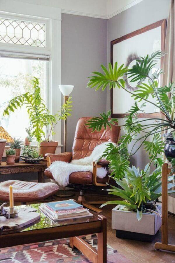 decoração de sala de estar com poltrona de couro e vasos de plantas Foto Archidea