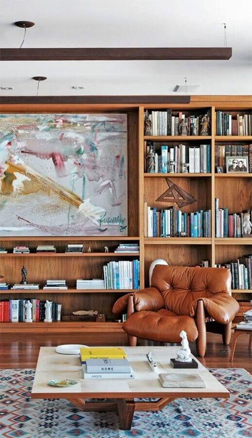 decoração de sala planejada com estante de madeira e poltrona de couro para leitura Foto Pinterest
