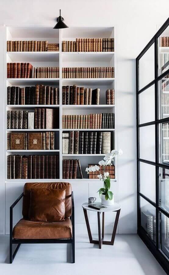 decoração minimalista com estante branca planejada e poltrona de couro para leitura Foto Futurist Architecture