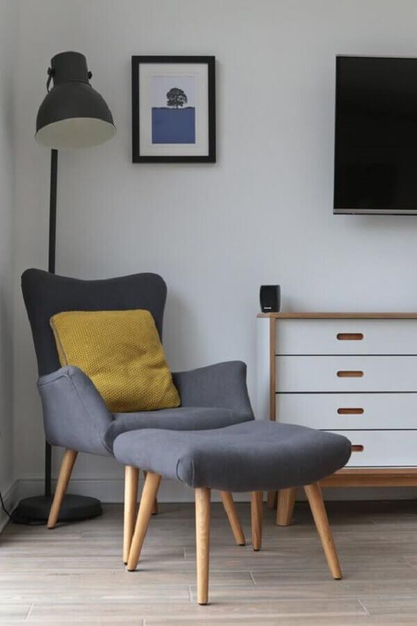 decoração simples com luminária preta e poltrona com puff para leitura cinza Foto Jeito de Casa