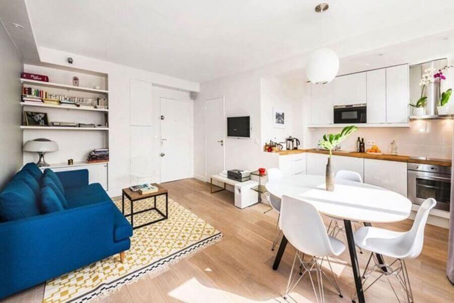 decoração simples com sofá azul para casa conceito aberto toda branca Foto Idealista