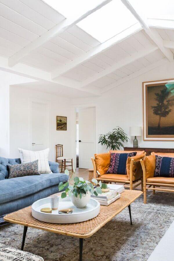poltrona de couro caramelo para sala de estar decorada com sofá azul claro e mesa de centro de fibra natural Foto Apartment Therapy