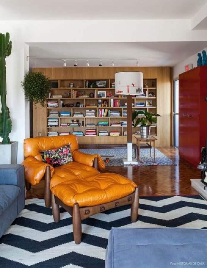 poltrona de couro caramelo para sala decorada com tapete preto e branco e estante de madeira Foto Histórias de Casa