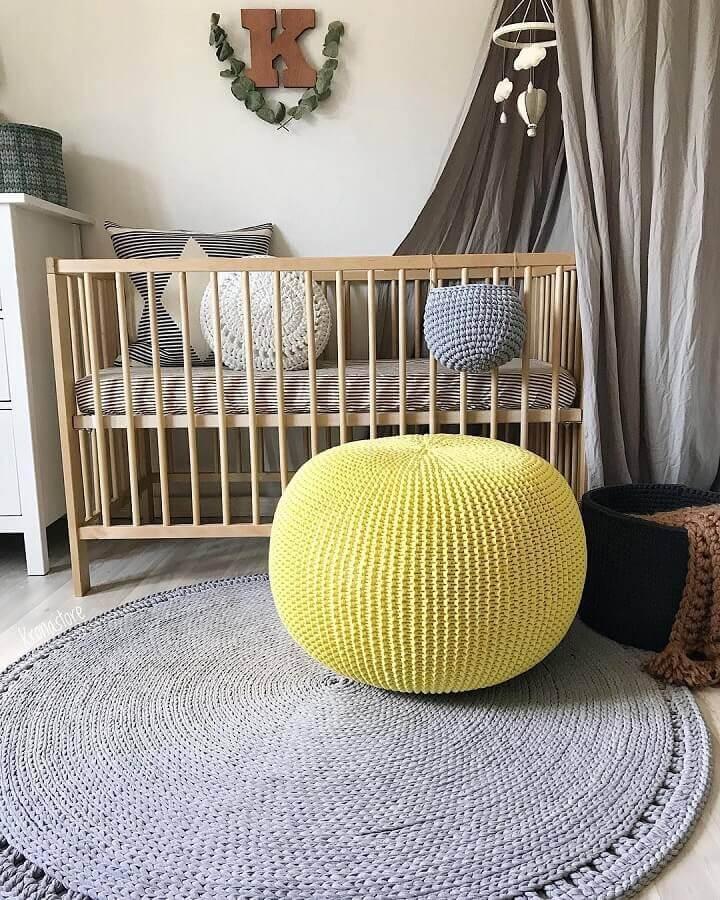 puff colorido para quarto de bebê decorado com tapete cinza e berço de madeira Foto Krona Store