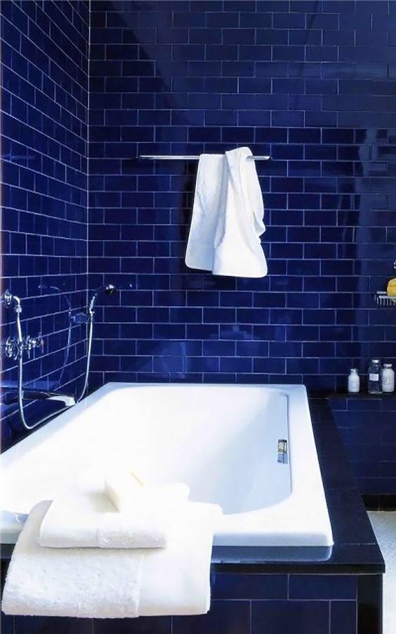Banheiro com revestimento azul marinho e banheira branca