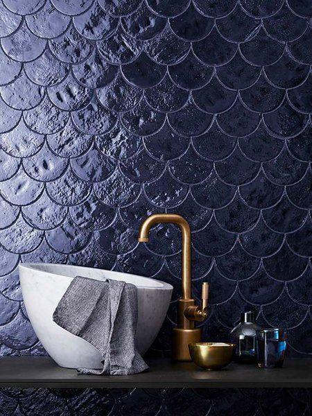 Banheiro em revestimento azul marinho com torneira dourado