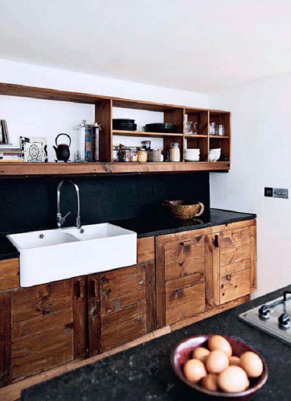 Armário de cozinha cor de madeira maciça e bancada de granito preto
