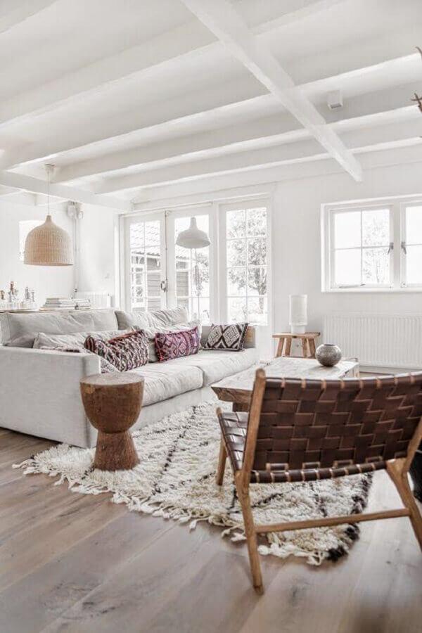 sala branca decorada com poltrona de tiras de couro e madeira Foto Apartment Therapy