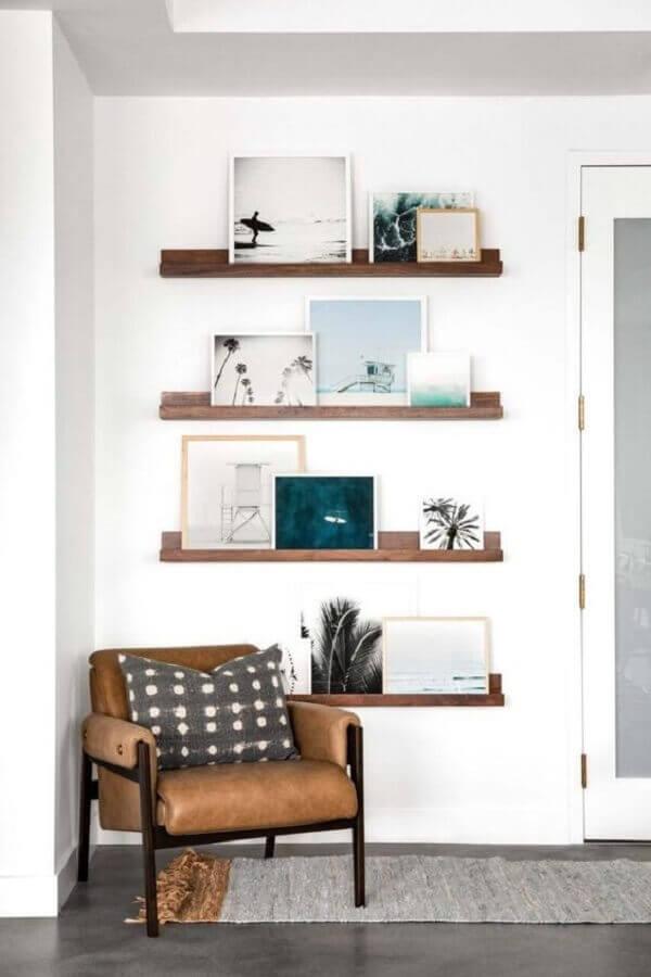 sala branca decorada com prateleiras de madeira e poltrona de couro Foto west elm
