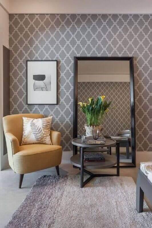 sala cinza decorada com poltrona bege e espelho de chão com moldura preta Foto Pinterest