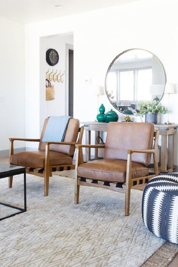 sala de estar clean decorada com poltrona de couro e madeira e espelho redondo Foto Style Me Pretty