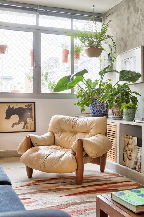 sala de estar decorada com parede cimento queimado e poltrona de couro marrom claro Foto Casa de Valentina