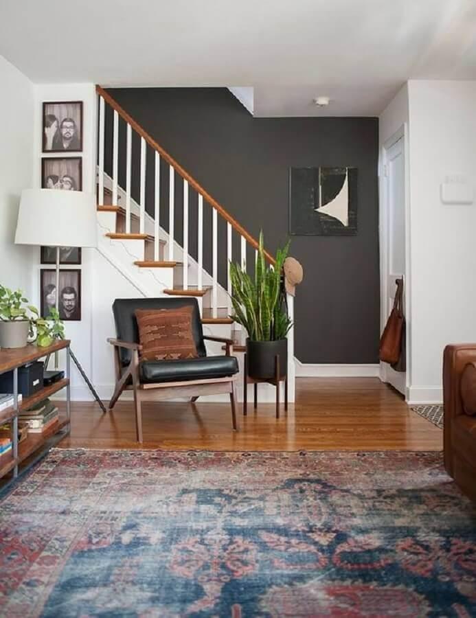sala de estar decorada com vaso de chão e poltrona de couro preta Foto domino magazine